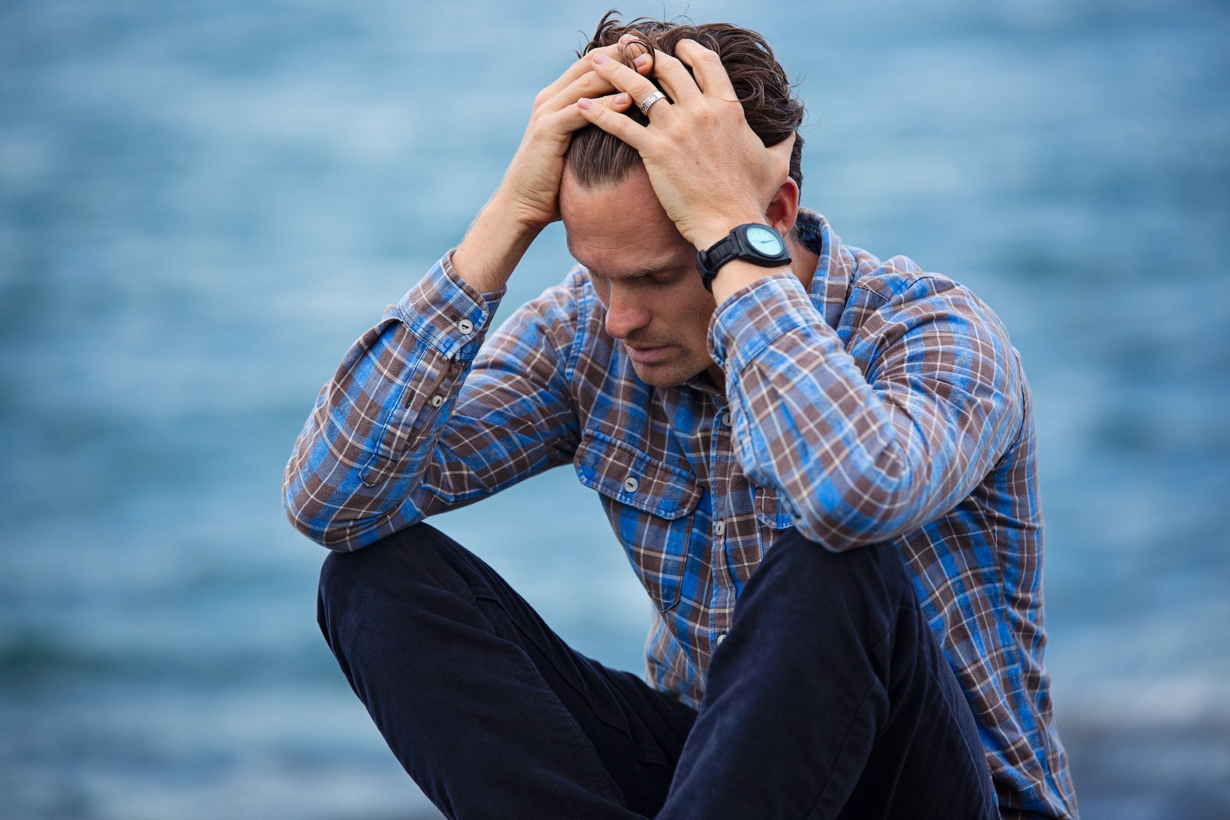 Frustrated man sitting down with his head in his hands on a blue background
